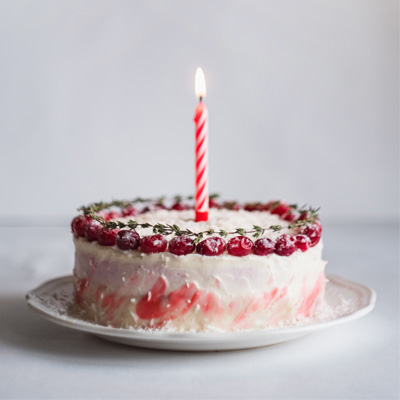 A colourful birthday cake with one candle in it