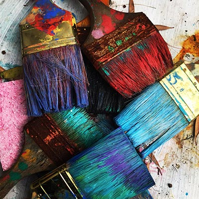 Several art paintbrushes with coloured paint on them