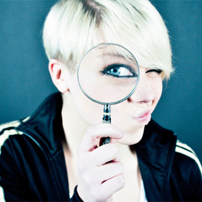 A female looking through a magnifying glass