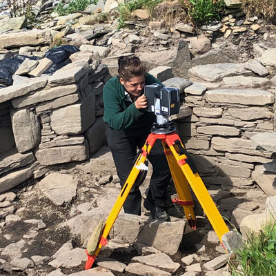 A male using archaeological surveying equipment outside