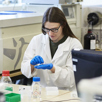 A female working in a lab wearing a white coat