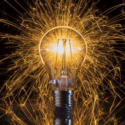 A lightbulb with several sparks emiting from it