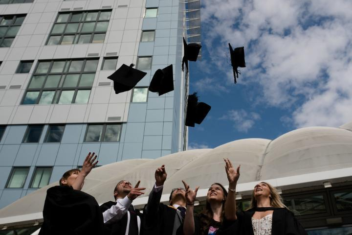 Graduates throwing caps in air outside Richmond building