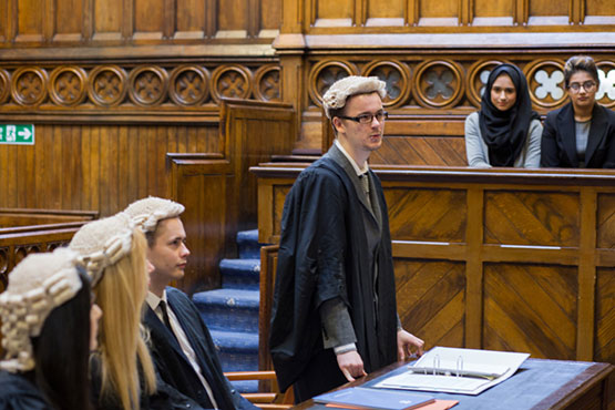 Law students taking part in a mooting session in a court room.