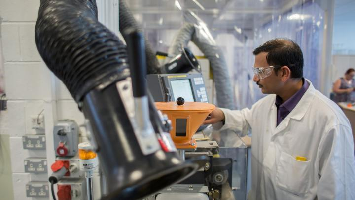 Researcher using injection moulding equipment