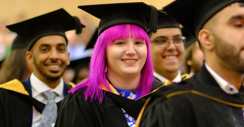 graduating student in full cap and gown with pink hair