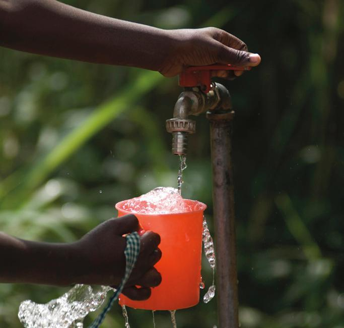 person filling a cup from an outside tap in Africa