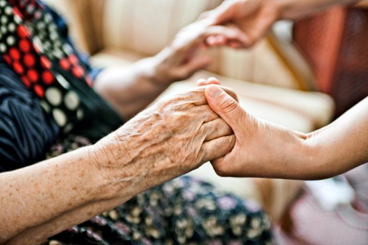 elderly ladys hands being held by younger person