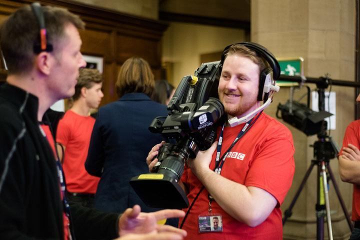 A smiling male student operating a television camera and wearing a BBC t-shirt